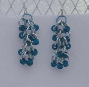 Anodized aluminum rings and glass beads colors: bright silver, sky, and matte teal beads beads weave: shaggy loops size: 1  5/8